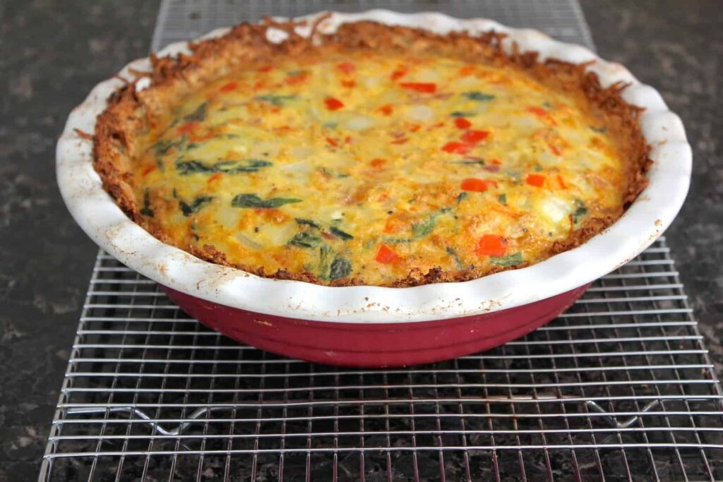 Baked ham and spinach quiche in a red ceramic pie plate.