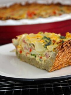 A slice of ham and spinach quiche on a plate.