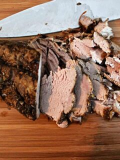 sliced pork tenderloin on a wooden cutting board