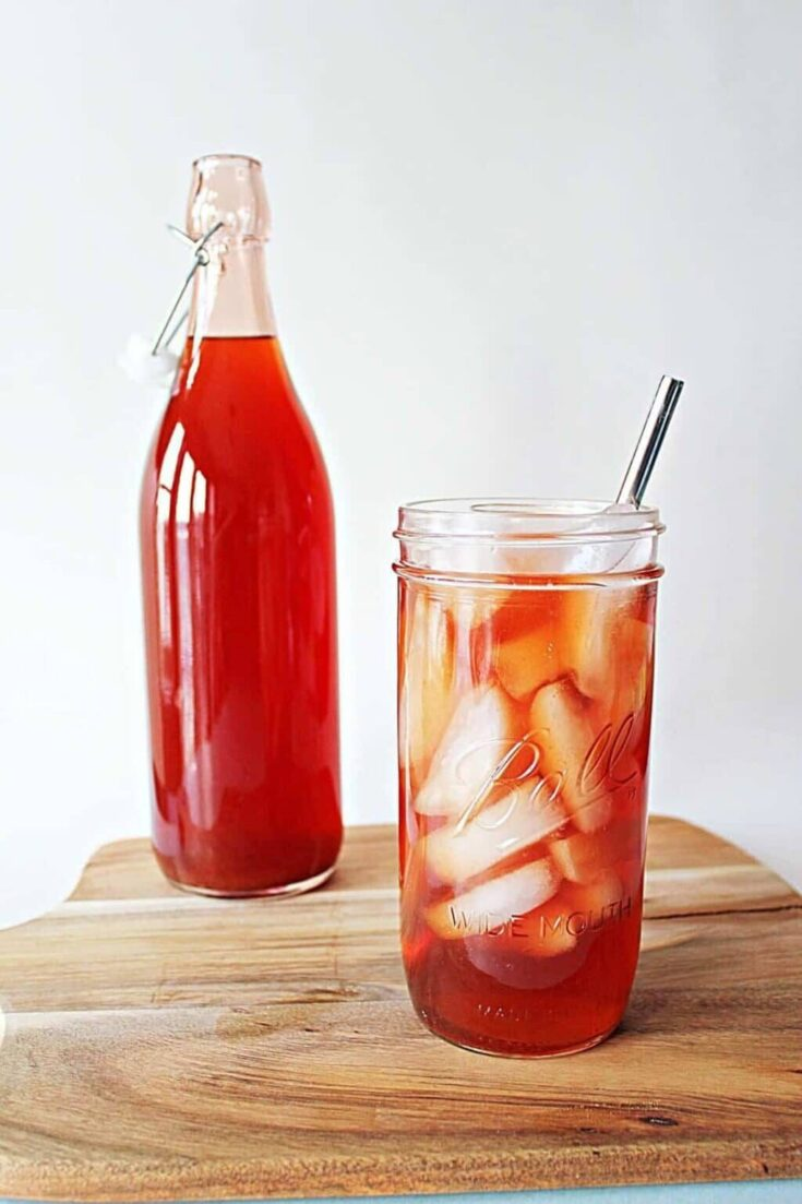 Strawberry iced tea in a mason jar filled with ice.