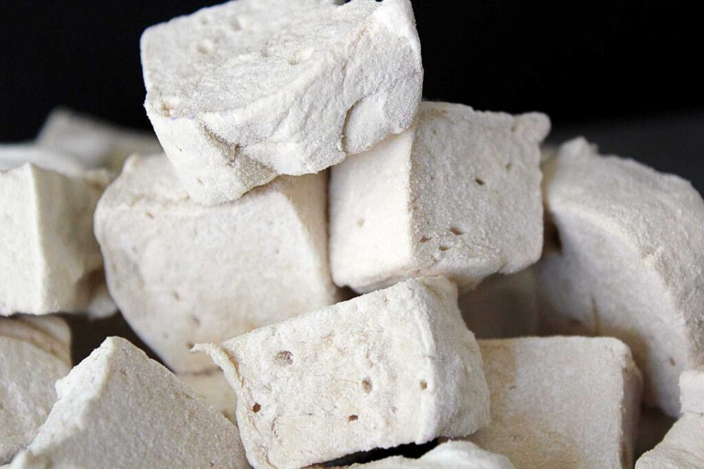 A stack of off white marshmallow cubes dotted with air pockets, and dusted with arrowroot startch against a black background