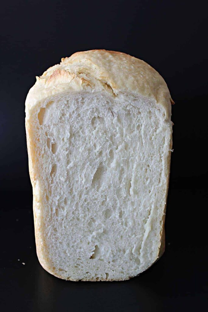 A cross section of a load of bread maker bread. The crust is the colour of pale straw with little golden brown bits where the crust has cracked and split. The crumb of the bread is white and filled with a mix of large and small air bubbles. It looks light and fluffy.