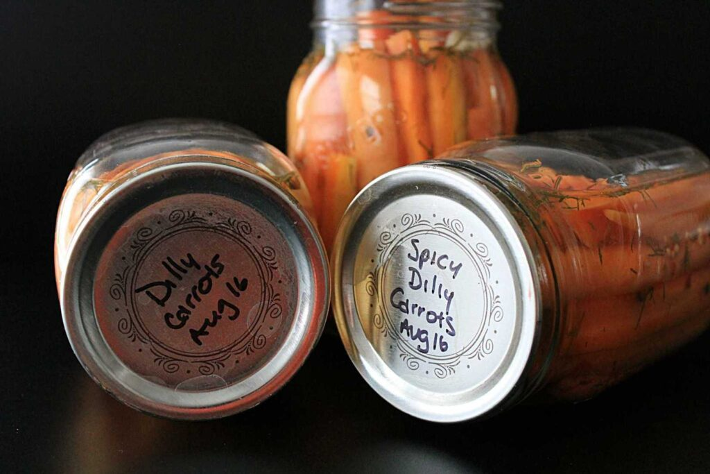 "two jars laying down, with lids facing you, the sliver lids are inscribed with ""Dilly Carrots Aug 16"", in the background is a jar filled with bright orange carrot sticks, flecked with small sprigs of dill, sliced white cloves of garlic, round brown cloves and peppercorns, and bright red pepper flakes against a black background"