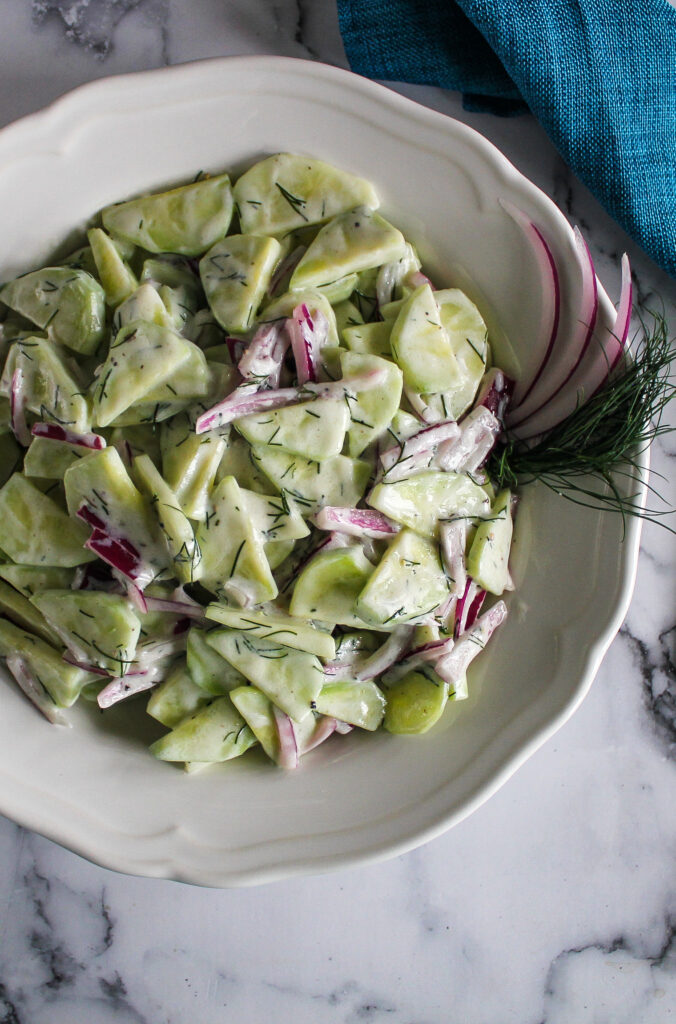 Creamy cucumber dill salad in a white bowl.