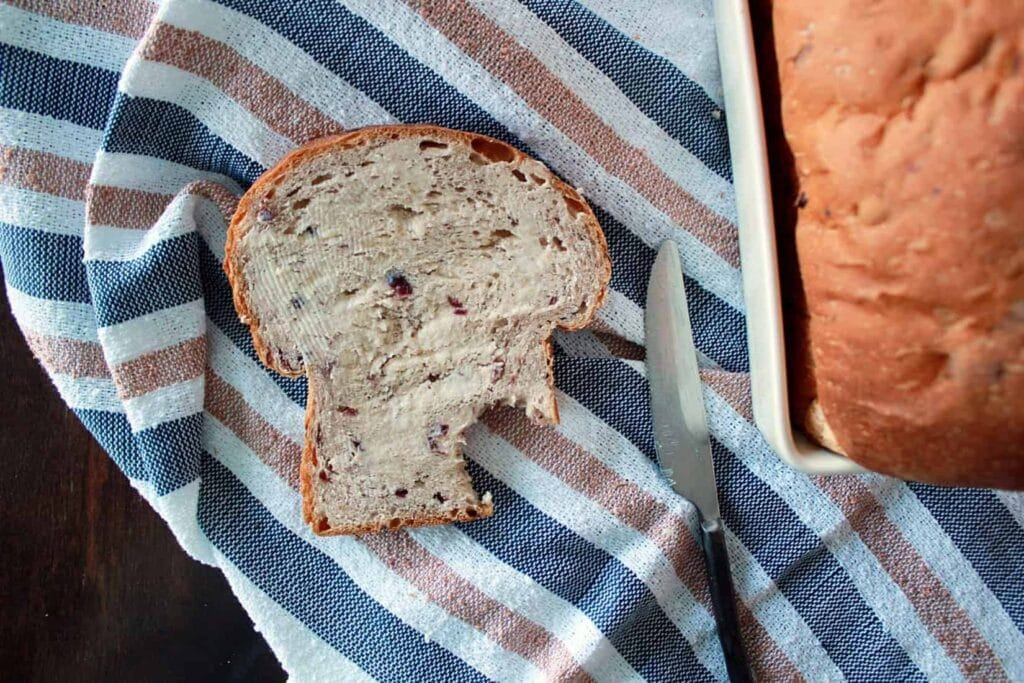 A buttered slice of bread machine cranberry bread missing a bite.
