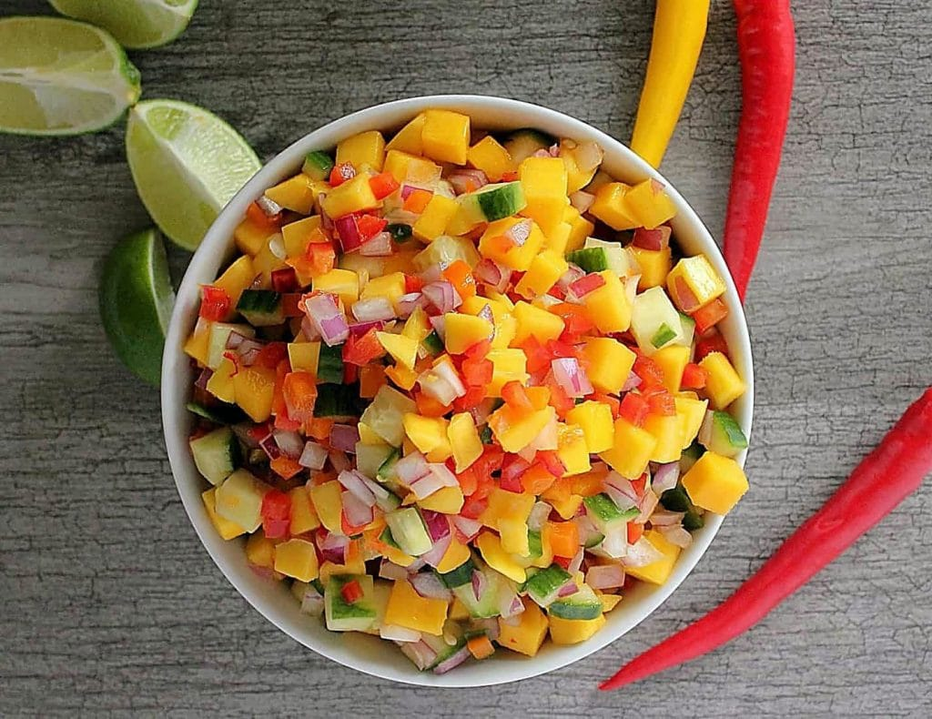 a white bowl filled with brightly coloured mango cucumber salsa. There are cubed pieces of all the ingredients, rich yellow mango, bright red bell peppers, pale green cucumber contrasted with a dark green peel and mini diced pieces of red hot pepper against a grey wooden background. There a quartered limes piled to the left of the white bowl.