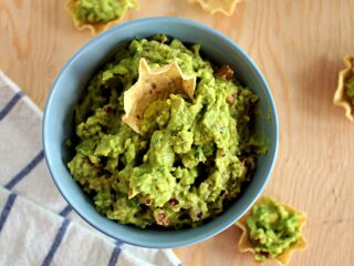 a beige tortilla chip scooping up bright green guacamole dip in a light blue bowl against a wood background