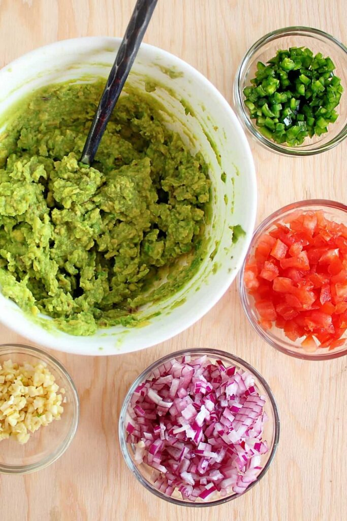 An overhead view of the ingredients used to make this guacamole recipe. The largest bowl is filled with coarsely mashed avocado, and it's surrounded by clear bowls containing diced green jalapenos, diced tomatoes, diced red onion, and minced garlic.
