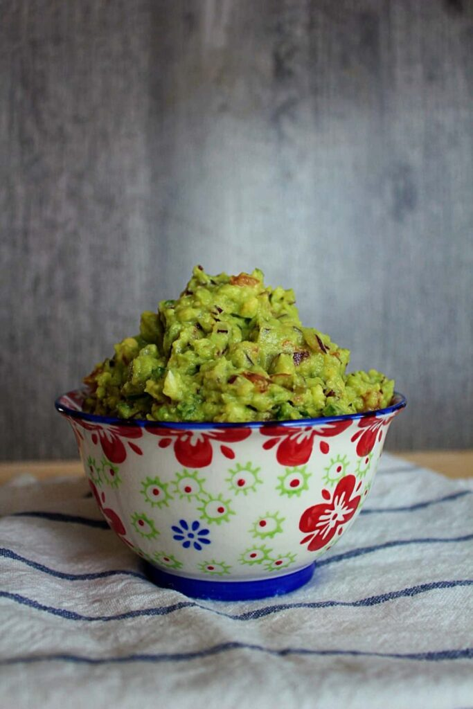 bright green guacamole dotted with chopped purple onion, red tomato, dark green jalapeños, creamy minced garlic, and piled high in a white bowl with blue trim and red floral pattern against a grey, worn barn-board background