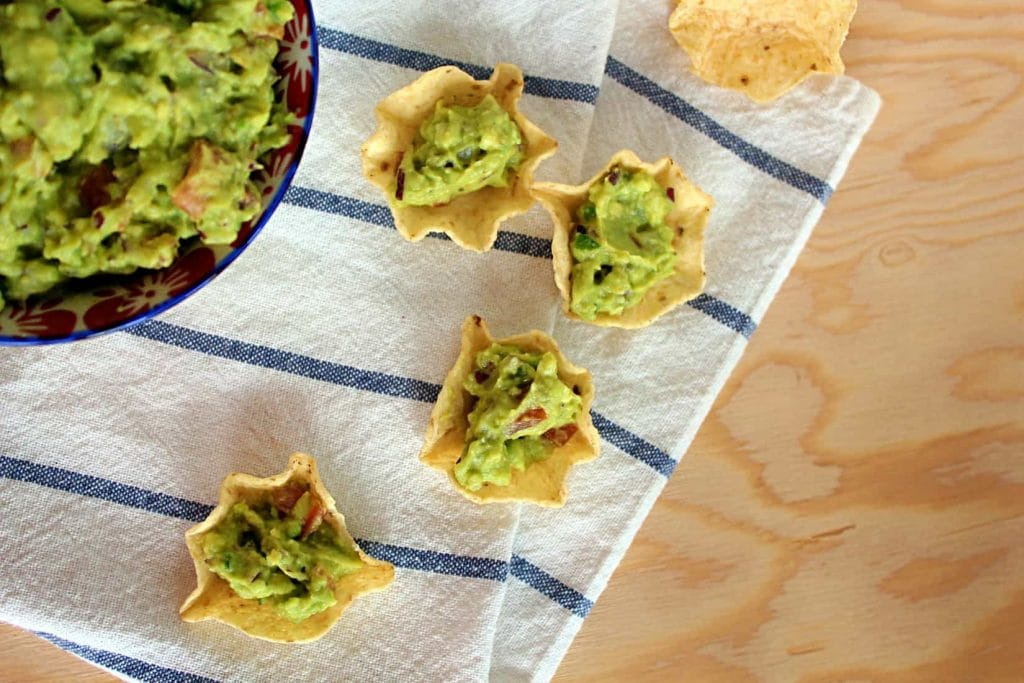 Nacho chips piled high with loaded guacamole.