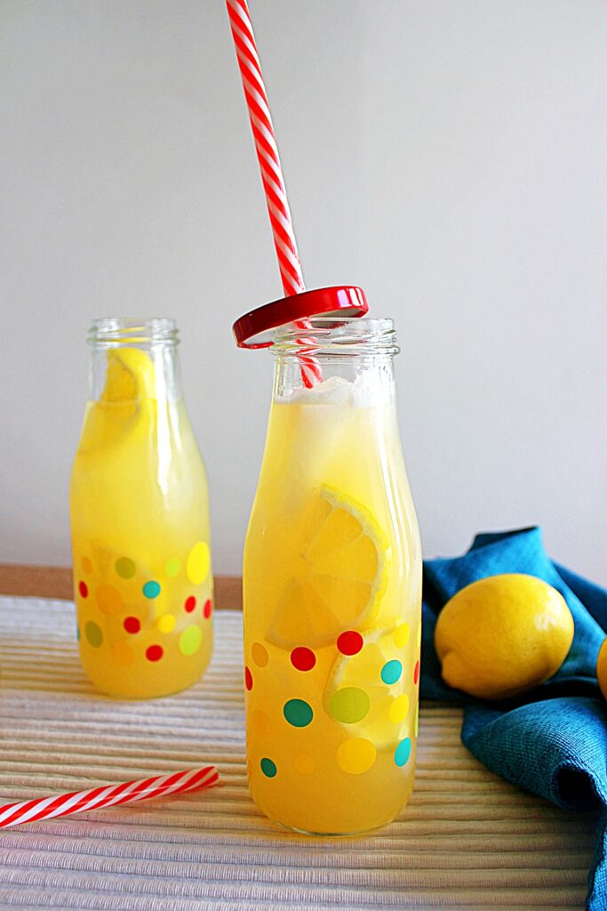 Two small bottles with multi coloured polka dots filled with ice, bright yellow sliced lemon and opaque yellow instant pot lemonade. One bottle has a red screw on cap with a red and white striped straw threaded through it. To the right of the photo is a gathered turquoise blue napkin with a bright yellow lemon sitting in it