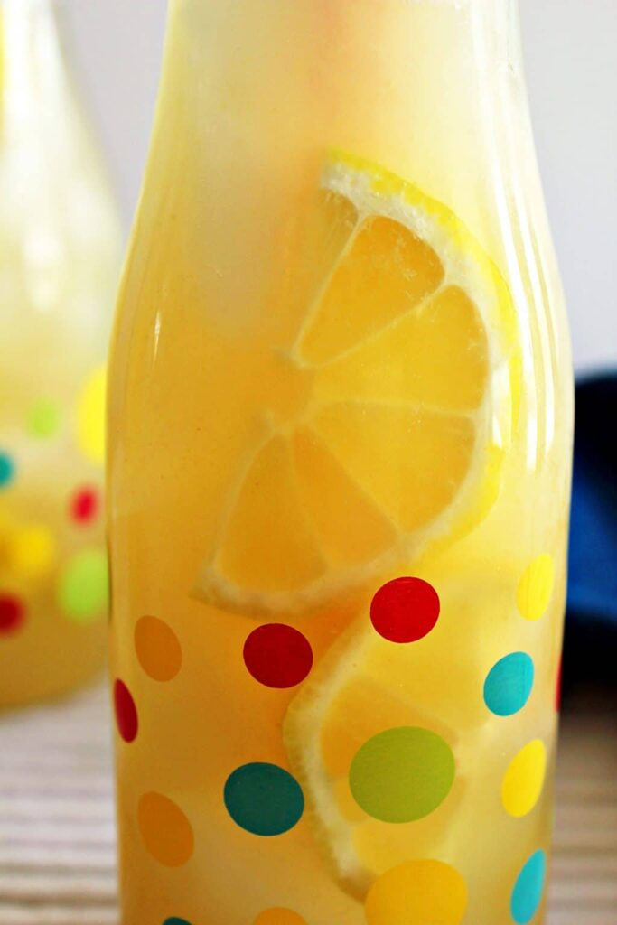 A close up view of small glass bottle with multi coloured polka dots filled with ice, bright yellow sliced lemon and opaque yellow instant pot lemonade. In this photo, you can better see the outline of the sliced lemons inside the lemonade.