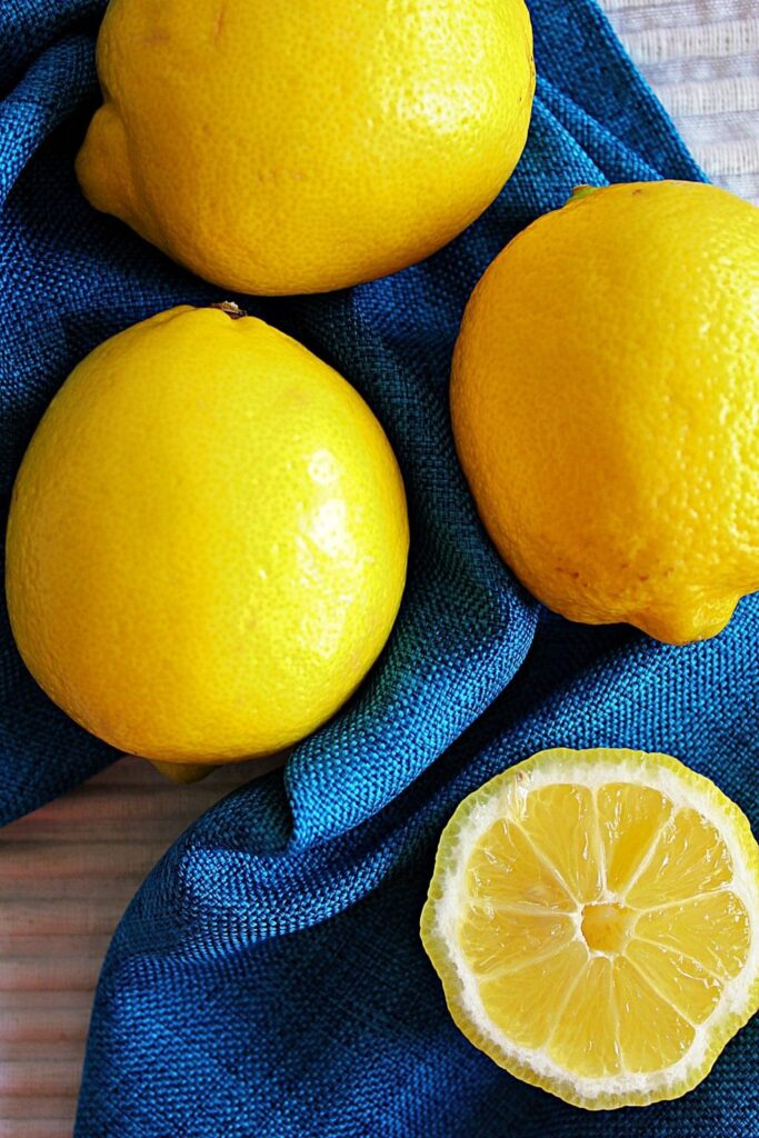 An overhead look at a bright turquoise napkin made of a crosshatched fabric is gathered with 3 whole shiny, bright yellow lemons on top. Near the bottom of the photo there is a cross section of a lemon, where you can see the vivid yellow rind surrounding the white pith, and the triangular segments of the lemon.
