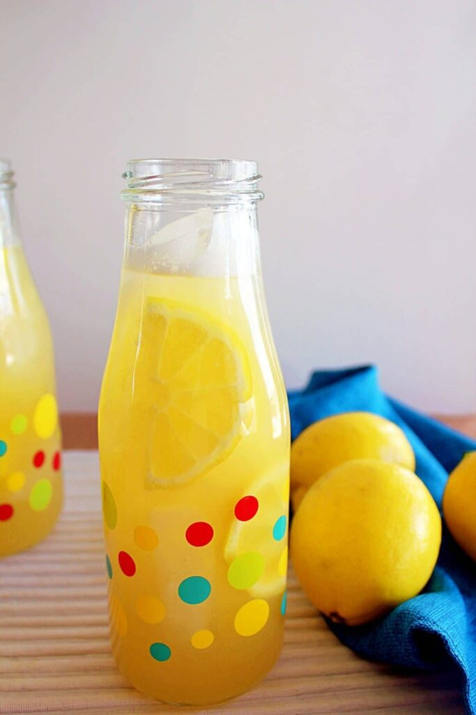 Two small bottles with multi coloured polka dots filled with ice, bright yellow sliced lemon and opaque yellow instant pot lemonade. To the right of the photo is a gathered turquoise blue napkin with three bright yellow lemons sitting in it