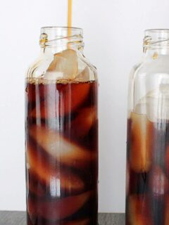 Pouring iced tea into a bottle filled with ice