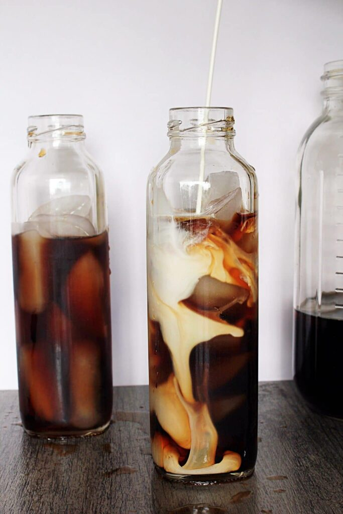 a tall narrow bottle filled with instant pot iced tea and ice cubes, and heavy cream swirling into the bottle