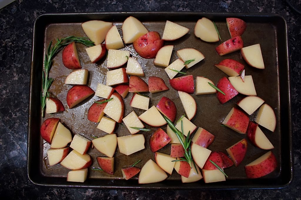 overhead view of red skinned potatoes on a baking sheet.