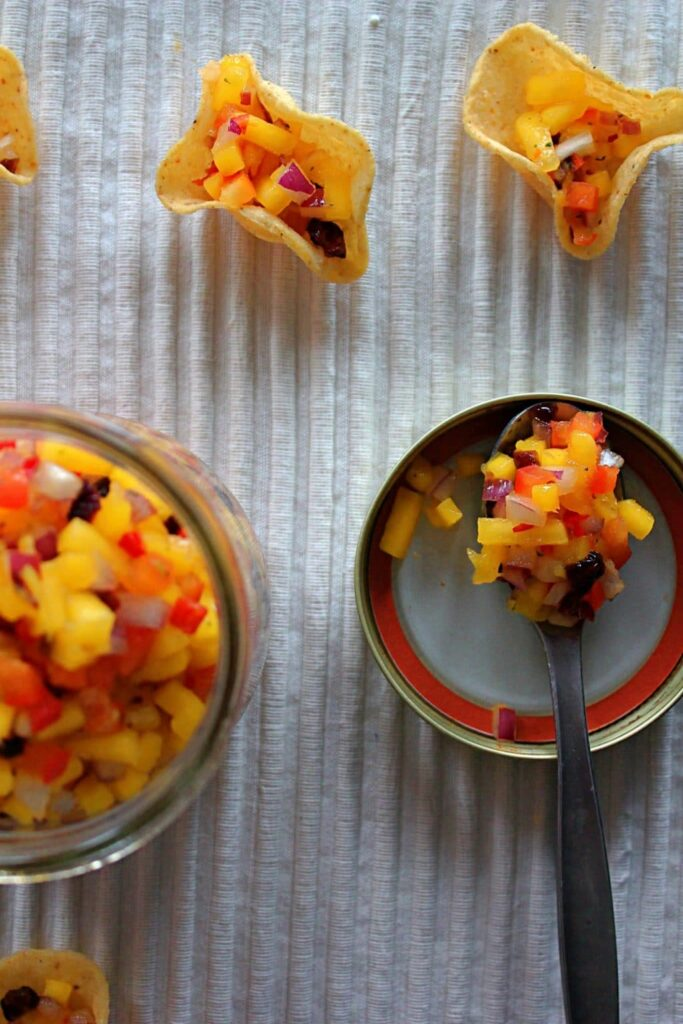 Focused view of spicy cranberry mango salsa piled high on a silver spoon resting inside the lid of a wide mouth mason jar sitting on a ribbed white placemat, and against a black background. The mango salsa is filled with perfectly diced vibrant orange-yellow mango, white onion flesh offset by a bright purple skin, really red bell peppers, and coarsely chopped burgundy dried cranberries.