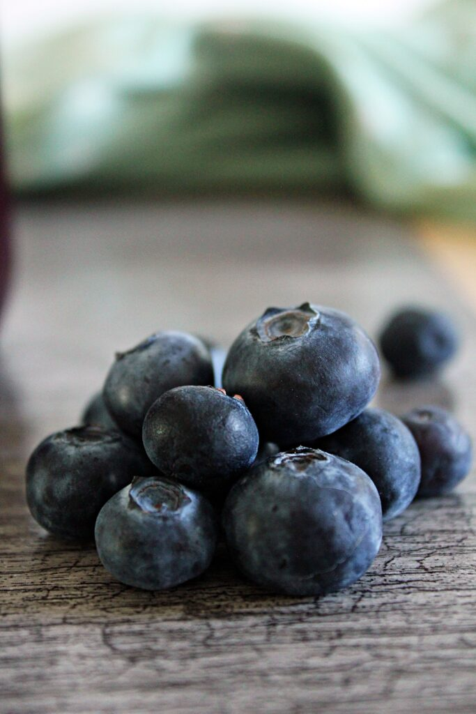 a pile of mixed sized blueberries on a wooden table.