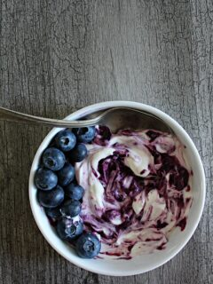 a white dish filled with yogurt swirled with instant pot blueberry jam.