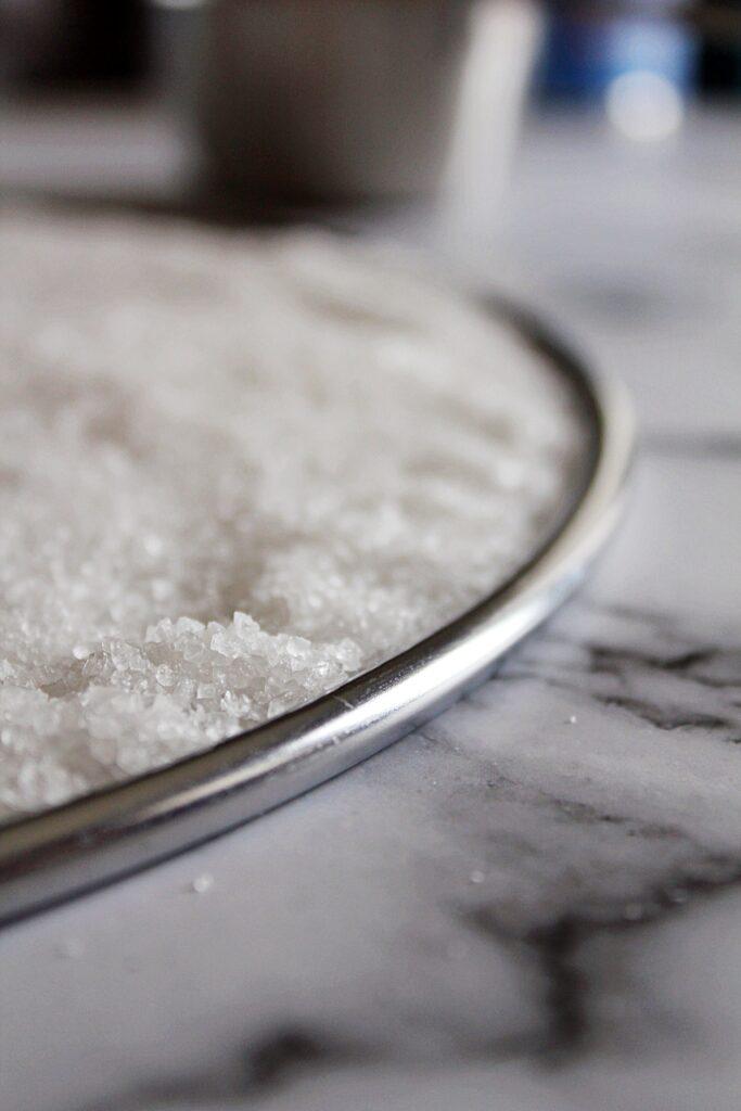 a close up of sea salt in a rimmed splatter screen.