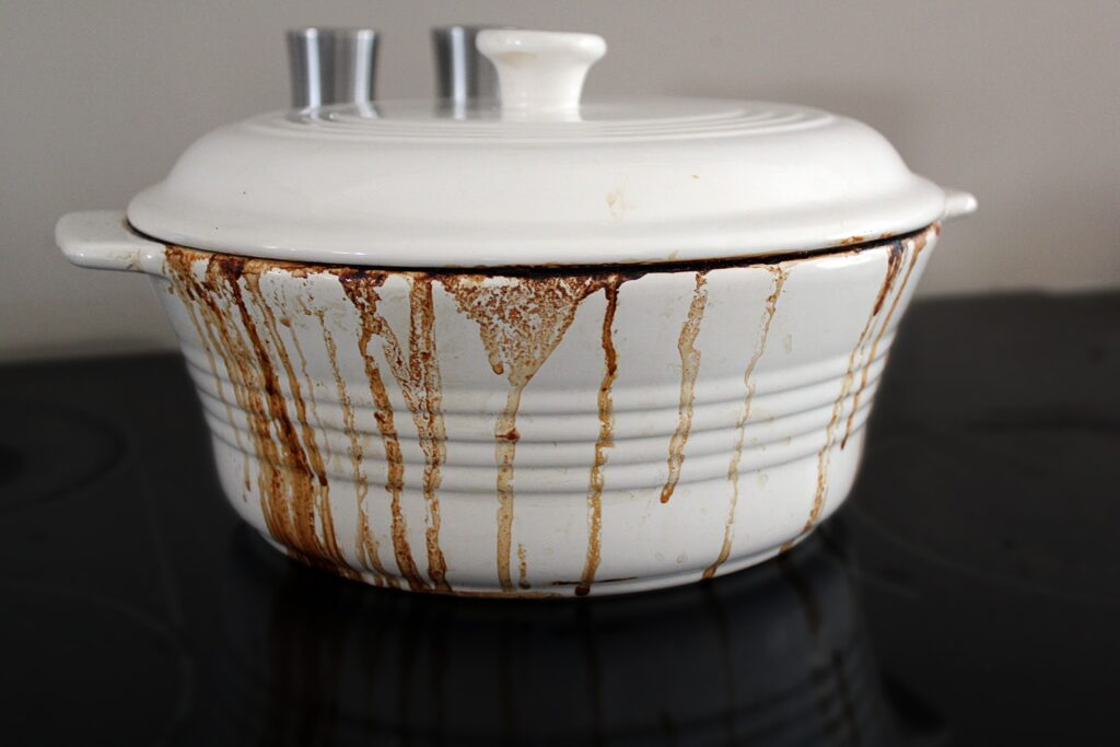 a white ceramic dutch oven with the lid on, dark brown chili had boiled over and streaked down the side of the rippled white edge of the pot.