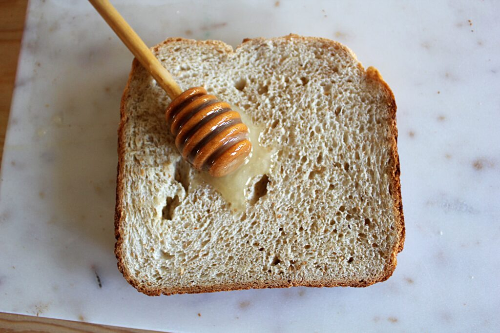 A honey dipper resting atop a slice of honey whole wheat bread. The crust is a golden brown and the honey has pooled on the hole filled surface of the bread.