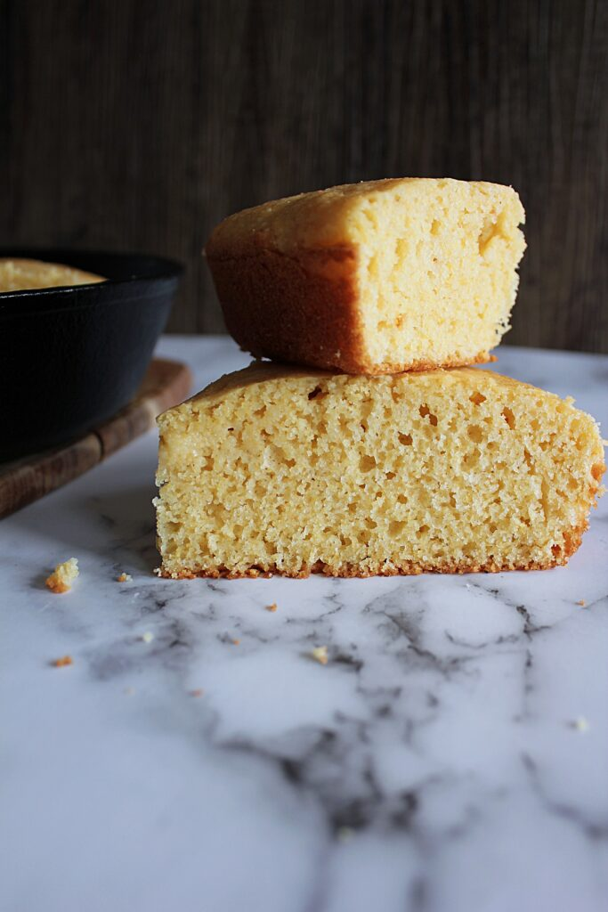 two wedges of yellow cornbread stacked on top of each other.