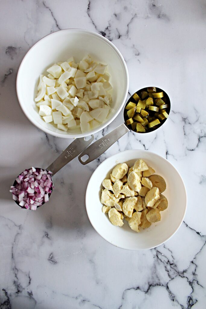 Chopped eggs, chopped pickles, diced onions, and halved egg yolks are all in their respective bowls, and the bowls are arranged in a square.