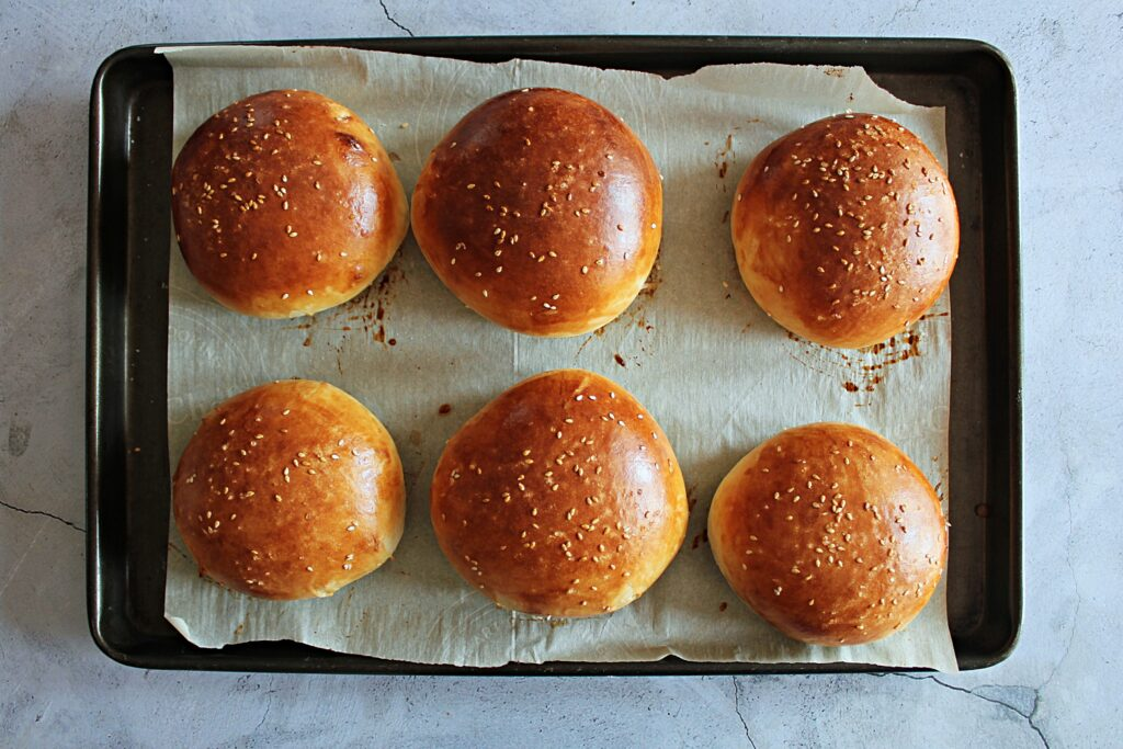 6 perfectly golden brown homemade hamburger buns. They are adorned with sesame seeds and sea salt.