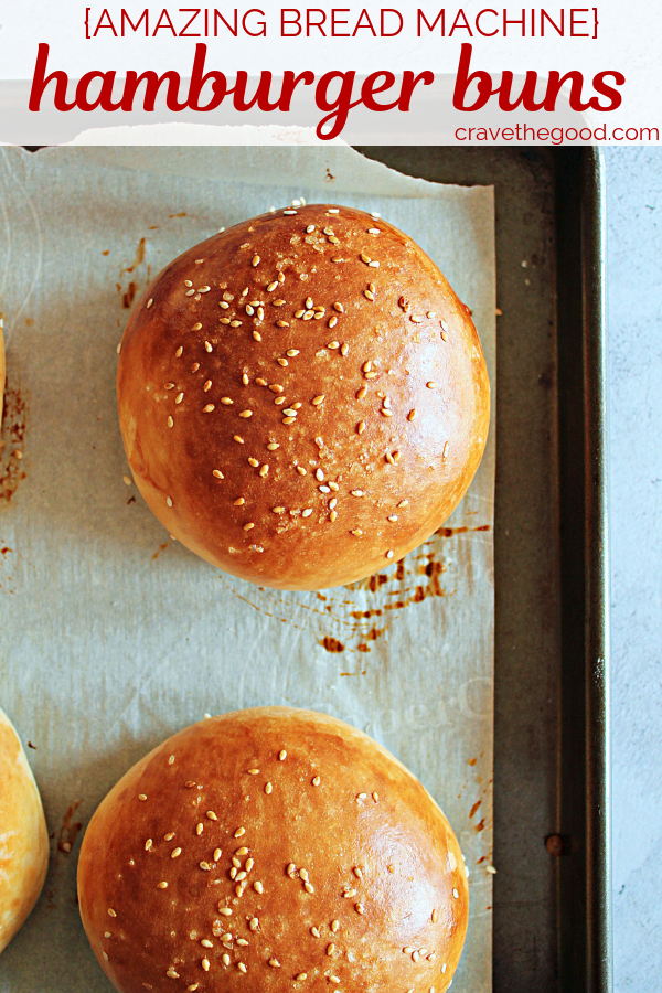 Close up of the homemade hamburger buns, they are golden brown with sesame seeds and sea salt sprinkled on top, with a Pinterest caption overlay stating the recipe title.