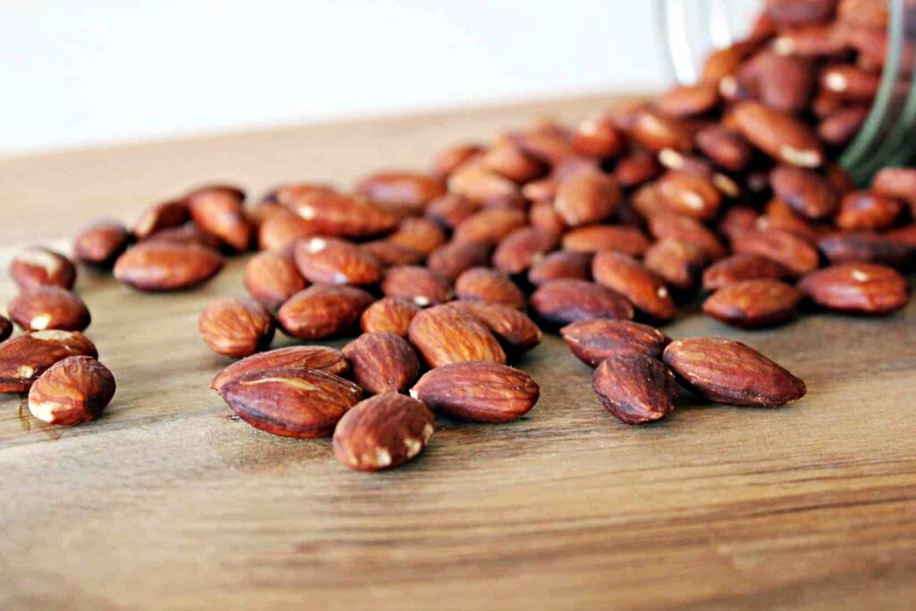 Mason jar tipped over with dark skinned almonds spilling out onto a wooden cutting board.