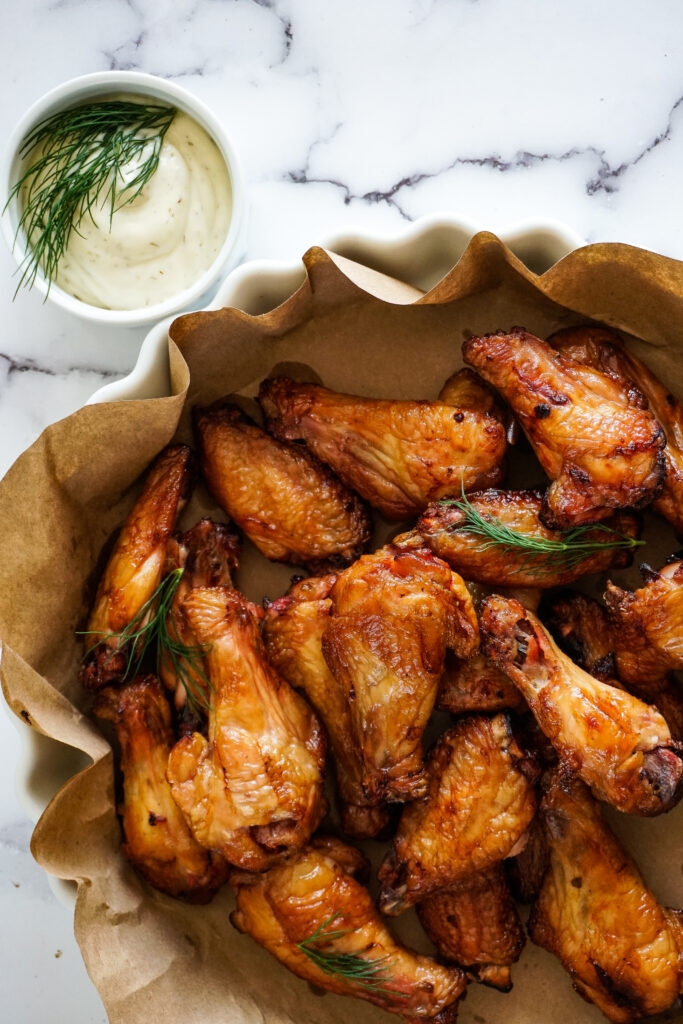 Crave the good dill pickle brined chicken wings in a white dish.