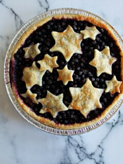 A dark berry pie with flaky pie crust star cut outs as the pie crust topper.