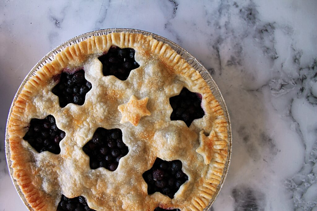 A blueberry pie with star shaped cut outs creating negative space in the flaky pie crust topping.