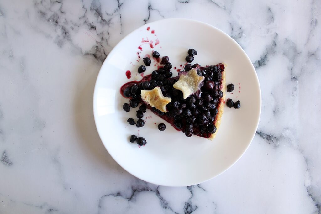 A slice of blueberry pie with flaky pie crust on a white plate.