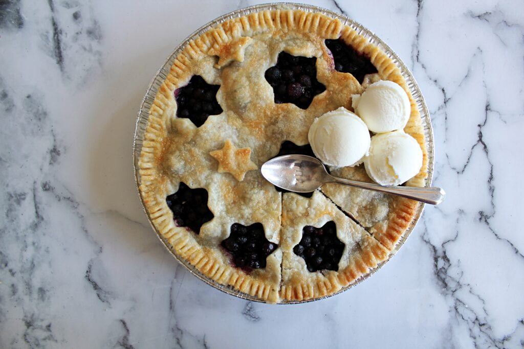 Blueberry pie with perfect pie crust that has a wedge cut into it, and 3 balls of ice cream on top.
