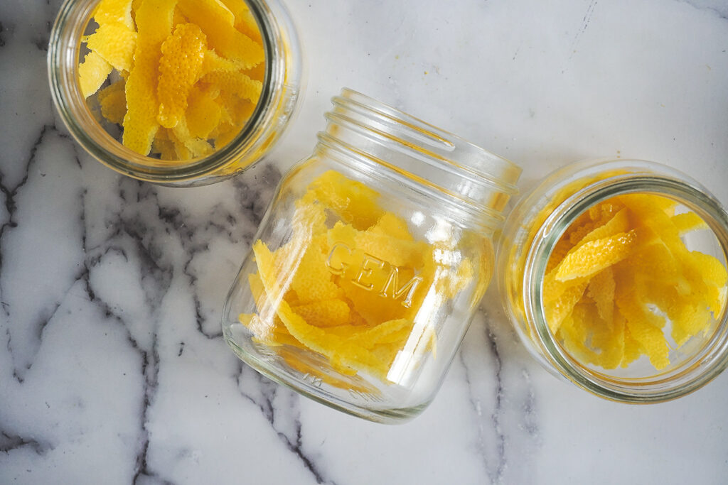 3 jars filled with bright yellow lemon zest.