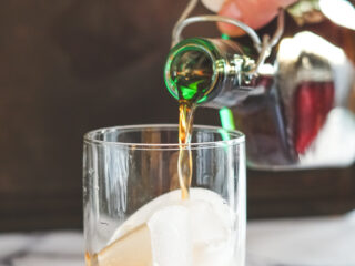 Pouring sous vide Kaluha into a glass with ice.