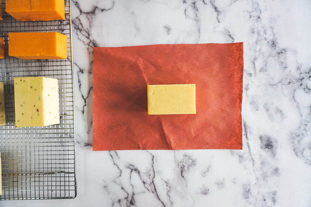A white block of smoked old cheddar cheese sitting on a piece of peach butchers paper.