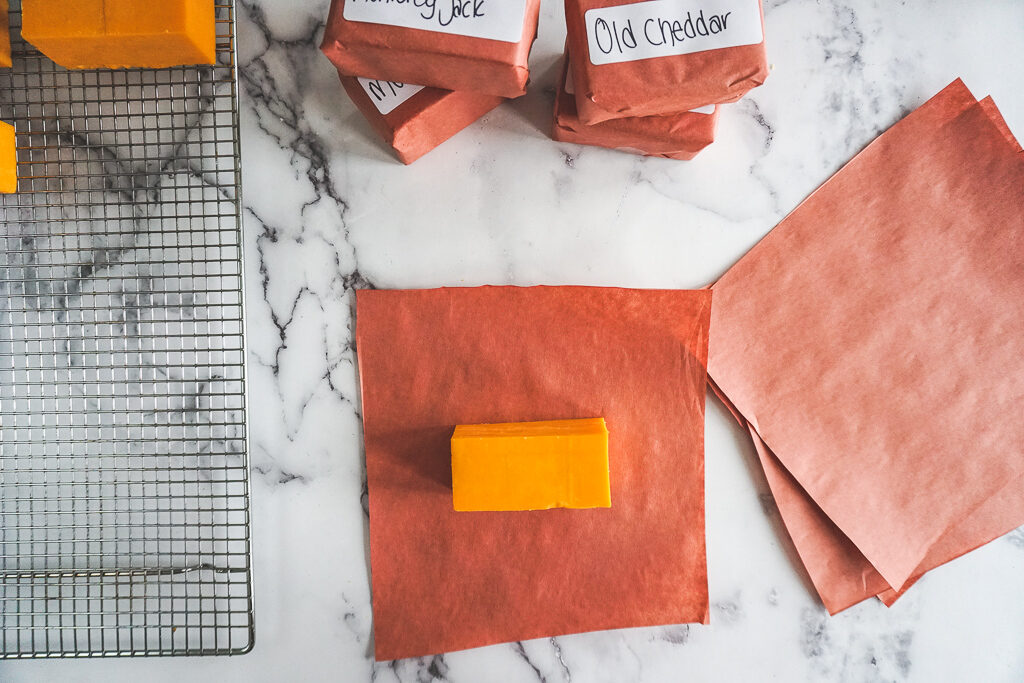 A block of orange cheddar on a square of butcher paper.