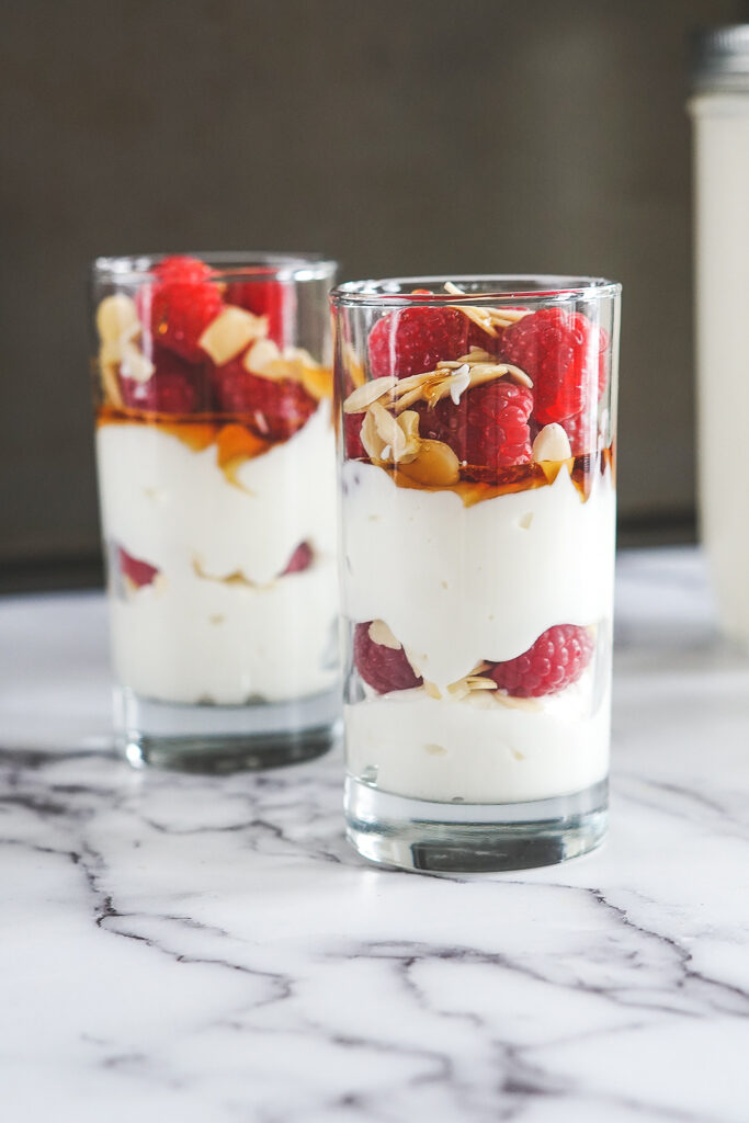 A sous vide yogurt parfait with layered yogurt, raspberries, sliced almonds and maple syrup drizzle.