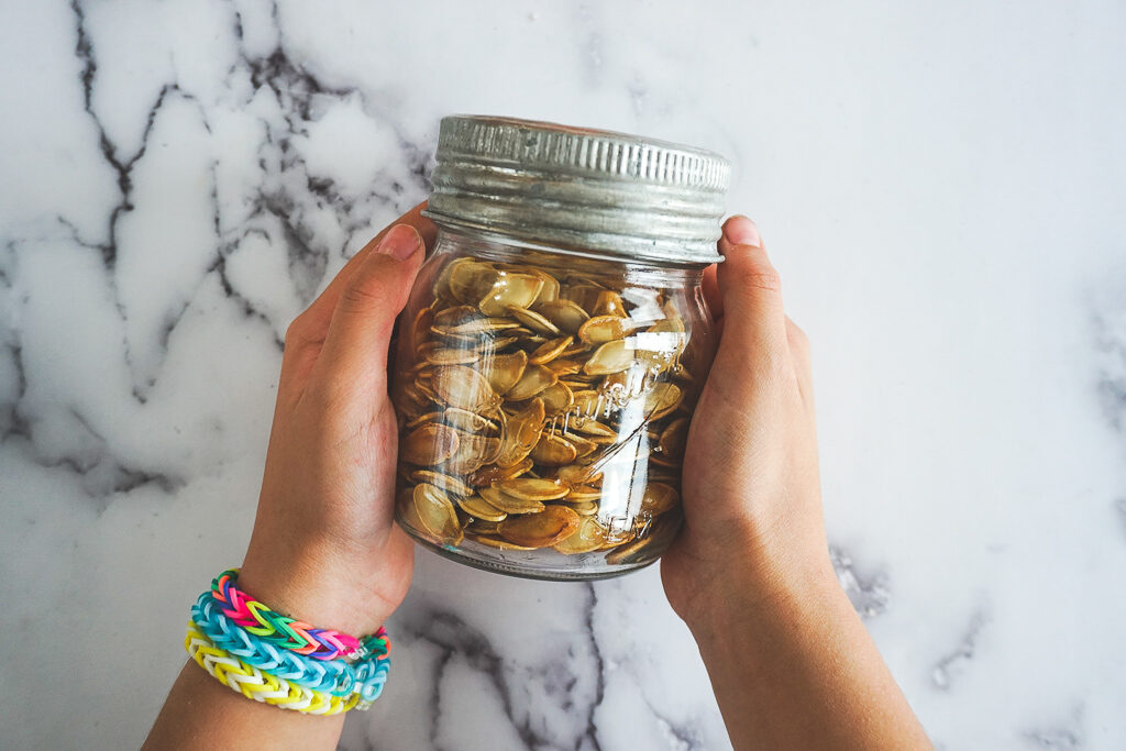 A child's hands holding a mason jar filled with smoked pumpkin seeds.