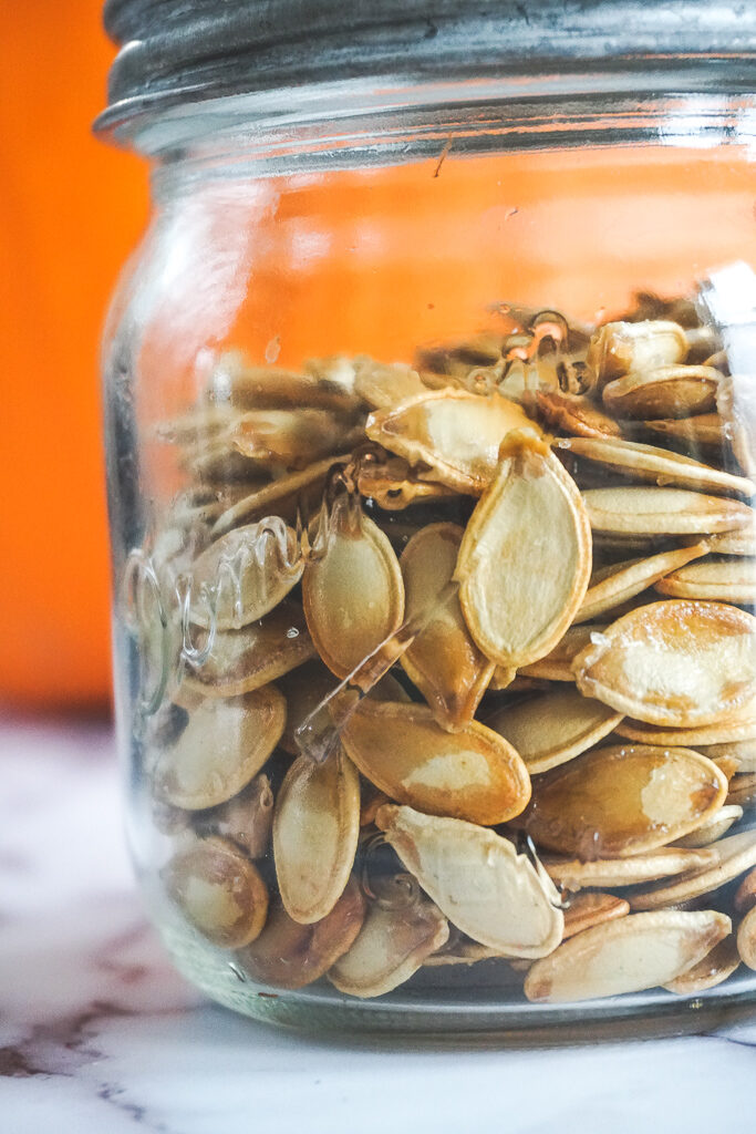 Close up of salted smoked pumpkin seeds in a vintage mason jar.