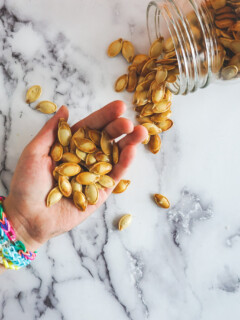 An outstretched hand holding smoked pumpkin seeds