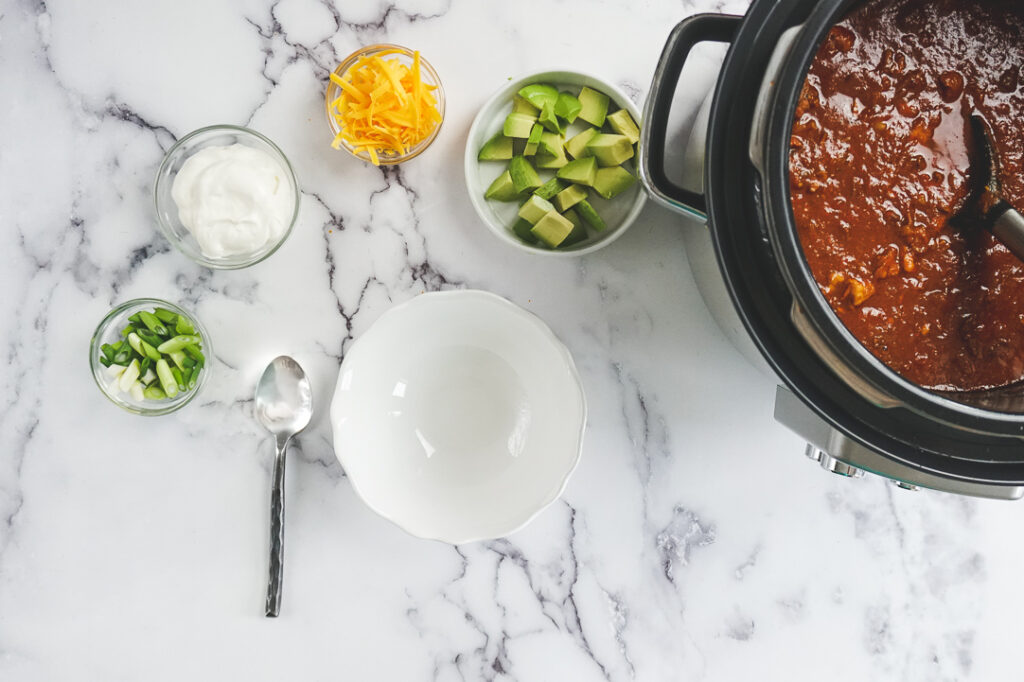 Cooked keto instant pot chili in the Instant Pot being ladled into a white bowl with toppings spread around the bowl.