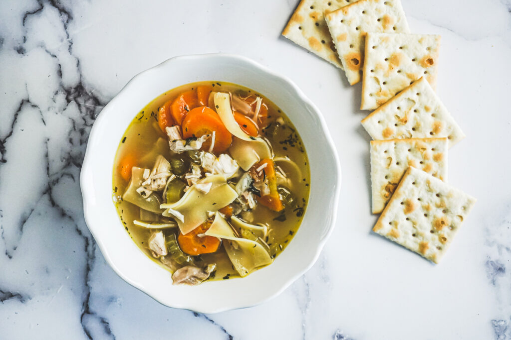 Instant pot chicken noodle soup in a white bowl surrounded by saltine crackers.
