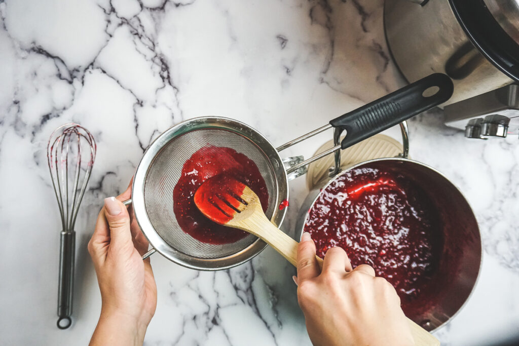 Cranberry glaze in a sieve with a spoon stirring and pushing the glaze through the mesh.