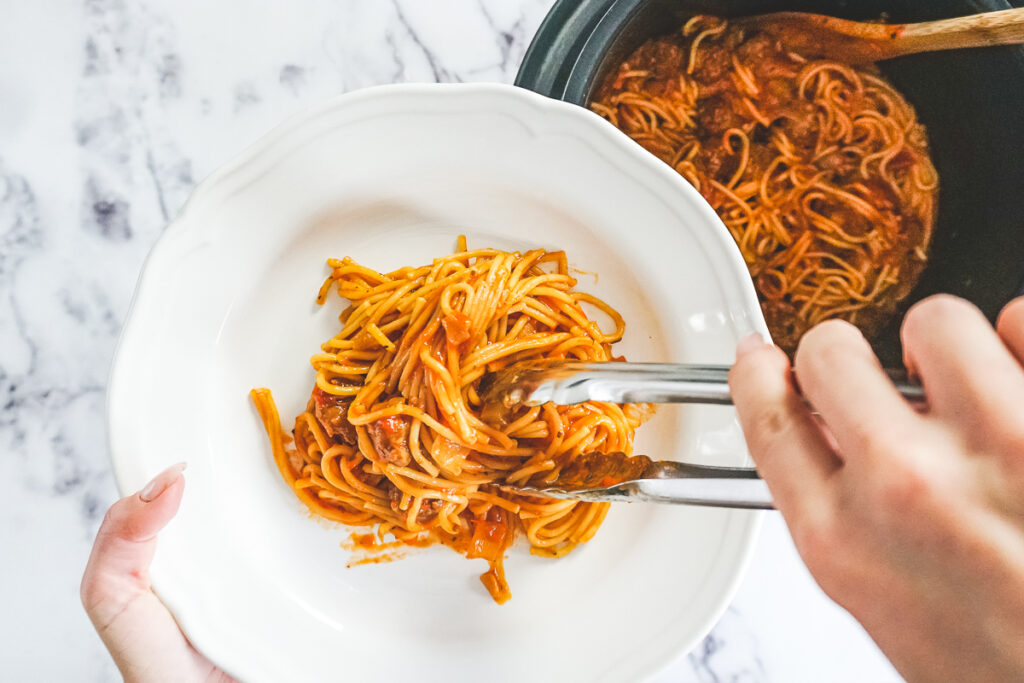 Tongs scooping spaghetti and meatballs from the instant pot and placing on a white dish.