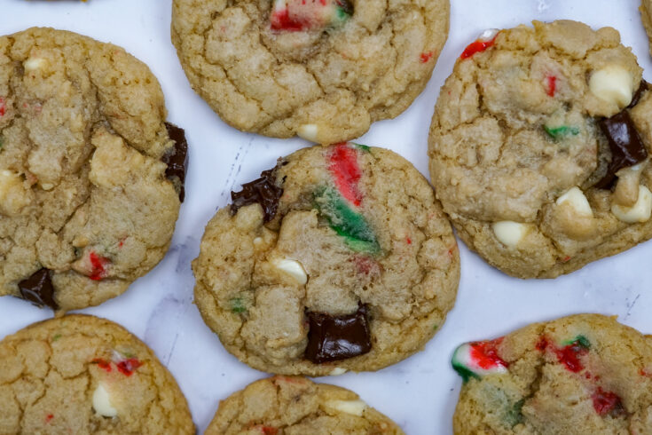 Candy cane cookies spread on the counter. Can see chunks of candy cane, white chocolate chips, chunks of chocolate.
